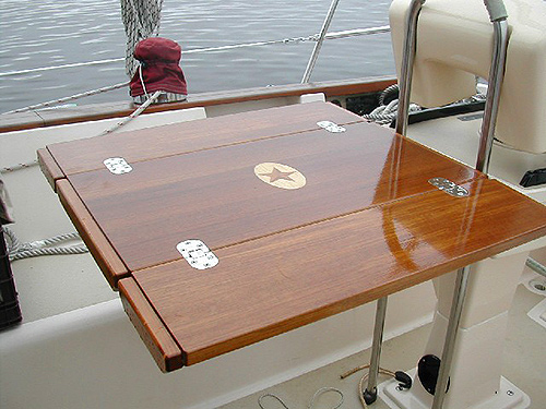 Folding teak cockpit table unfolded with inlaid design visible