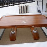 Three-piece folding teak dining table with leaves folded